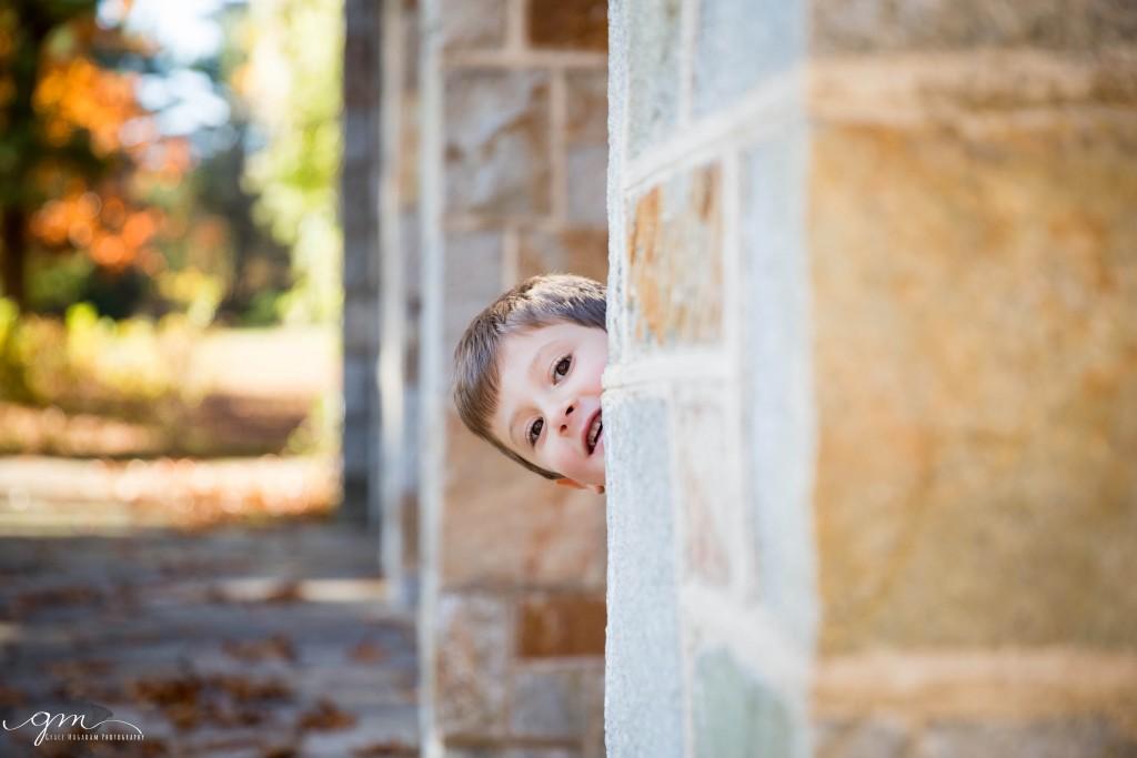 boy peeking around a stone wall