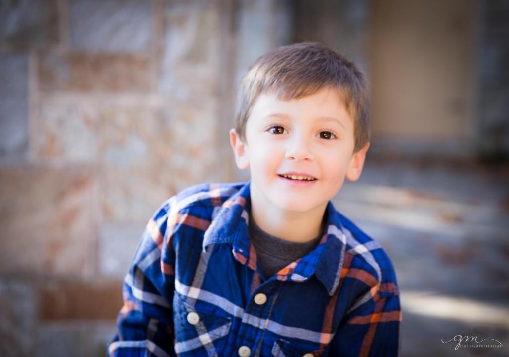 smiling boy in plaid shirt