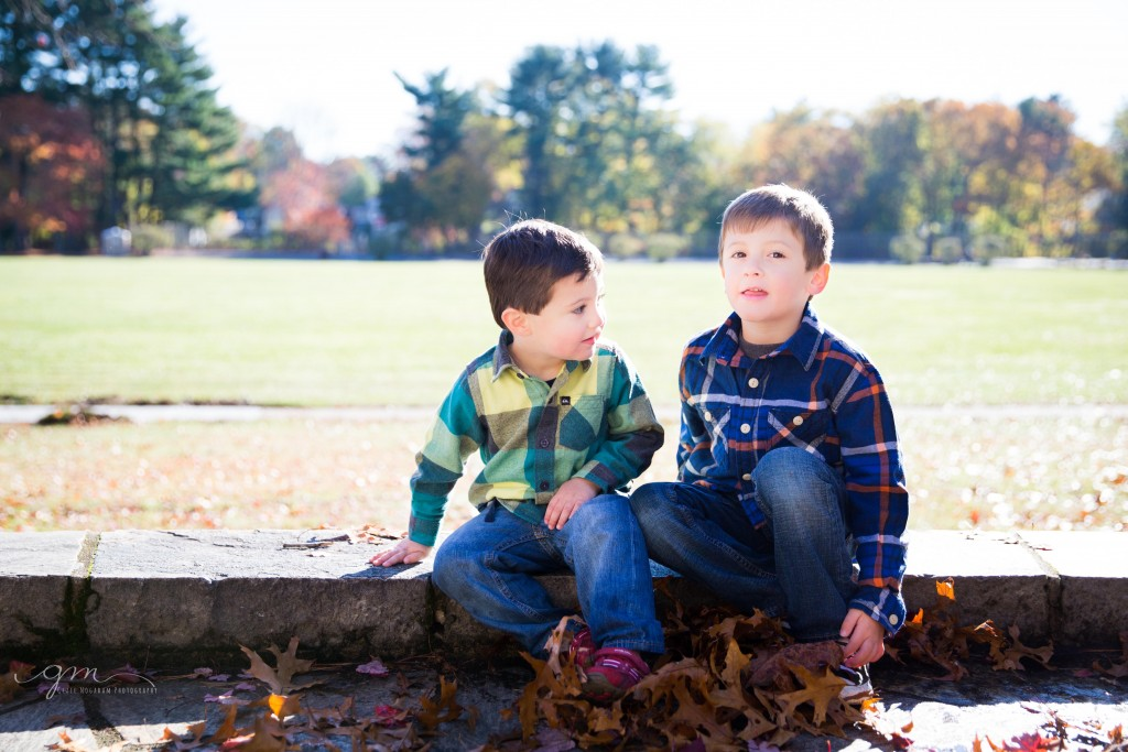 two brothers sitting on rock wall