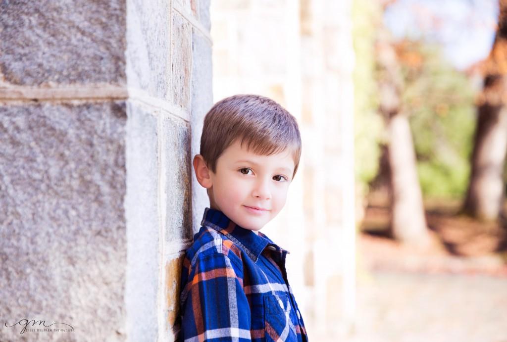 boy leaning against stone wall